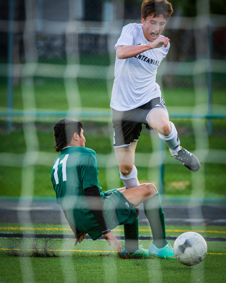 Colin Robinson (6), Senior, Midfielder, leaps over a North player attempting a slide tackle in the second half of the Ankeny Centennial High School Boys Varsity Soccer Team versus North High School game.